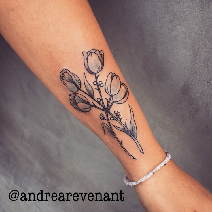 Delicate tulip tattoo by Andrea Revenant