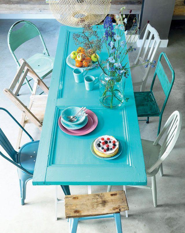 Bela mesa feita de porta e pintada de azul. Cadeiras variadas ficam um charme.