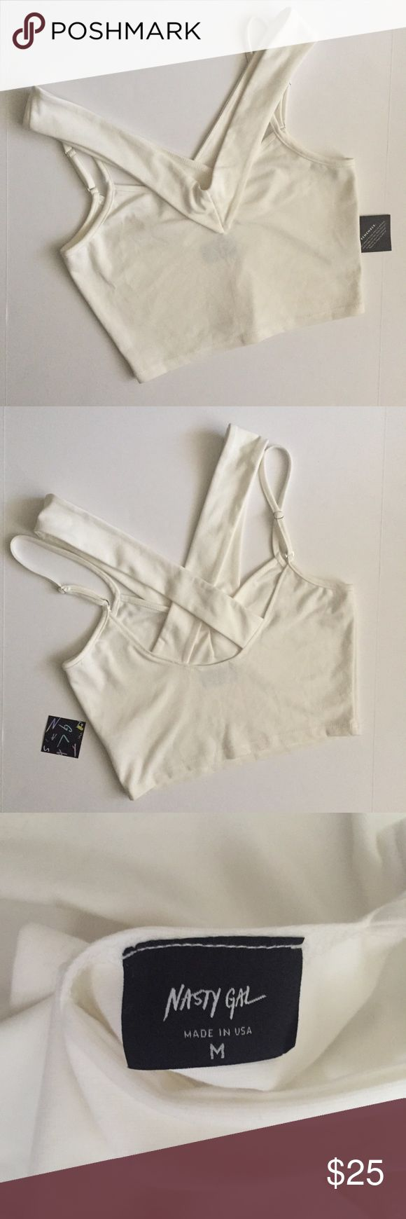 """White/cream strappy crop top by Nasty Gal size M Soft crop top with cross cross straps around back and adjustable spaghetti straps in a white/cream color.  Stretchy material!  Size M By Nasty Gal  Brand new, one original tag still attached.   Measurements are approximate (flat lay): Armpit to armpit- 16.5"""" Length (shoulder to hem)- 17""""  Color may vary in person from pictures and between screens Nasty Gal Tops Crop Tops"""