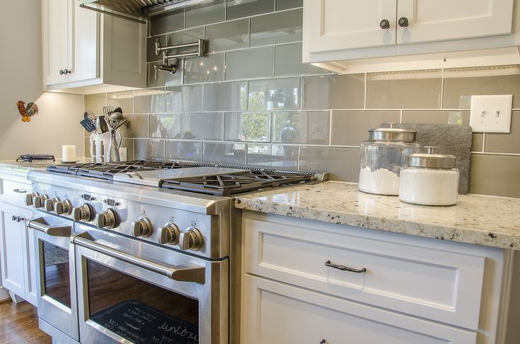 White kitchen countertops with a stainless steel gas range and pot filler. The backsplash is a gray ceramic tile with white grout #farmhouse ©Balducci Additions and Remodeling
