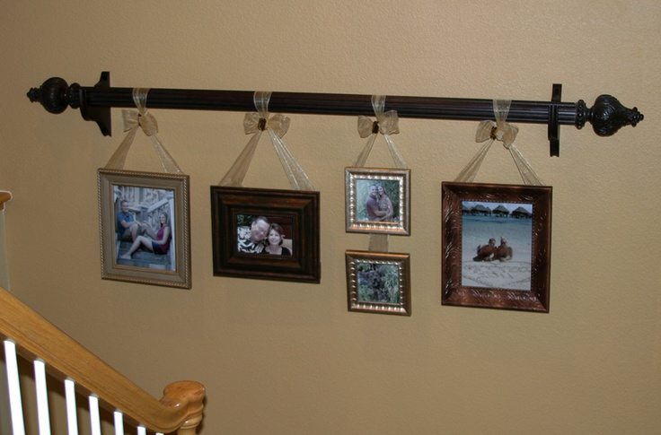Use ribbon to hang frames from a curtain rod great idea