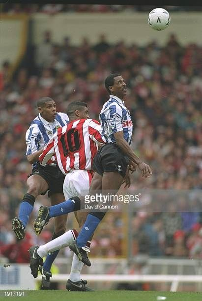 Viv Anderson of Sheffield Wednesday jumps highest to head the ball while team mate Carlton Palmer and Brian Deane of Sheffield United look on during...