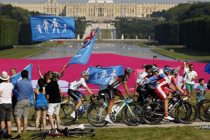 Le Tour de France, c'est aussi de la politique. Les militants attendaient les coureurs dans les allées du parc du château de Versailles Photo AFP.