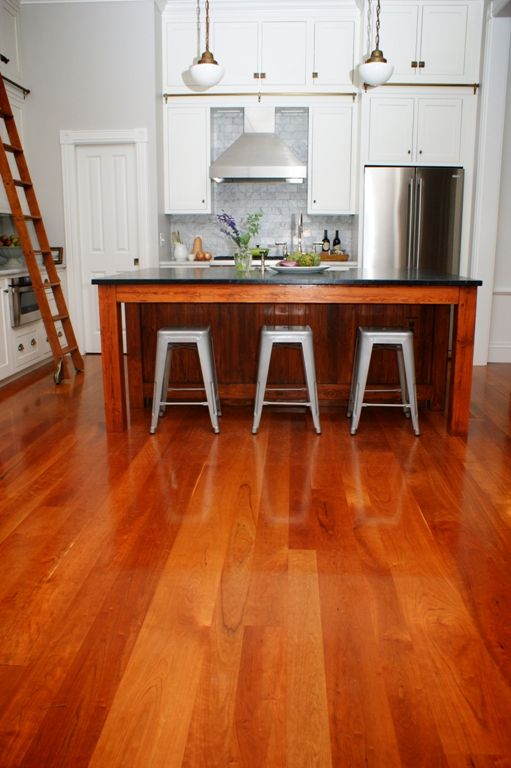 Solid hardwood Cherry floors bring warmth to a white kitchen.