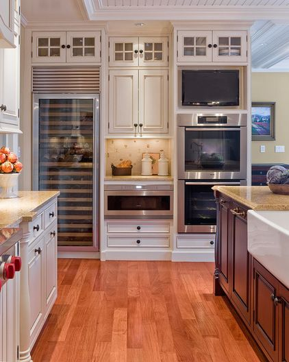 I'm a big fan the tall wall. Get all of these appliances in one spot to it make the other parts of the kitchen feel more open and airy. Here you have a double oven, microwave drawer, TV and wine refrigerator all tucked nicely into to one station.
