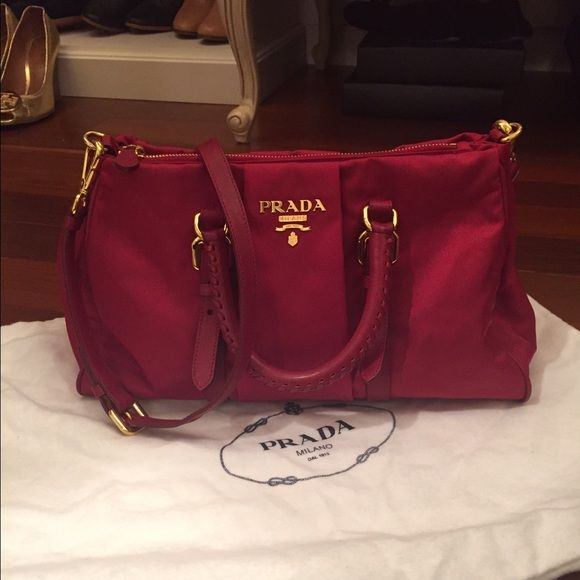"Prada nylon and leather satchel/shoulder bag Prada tessuto (nylon) and leather satchel / shoulder bag. Beautiful, rich red color. Nylon body with leather accents, handles and strap. Gold logo and hardware. Red logo pattern lining. Single interior zip pocket. Length is approx 12.5"" at bottom, 10.5"" at top. Height approx 7.5"". Handle drop approx 3"". Strap drop approx 17-18"". Love this bag because it can be worn casual or dressy. Used a few times; in excellent like-new condition. Cannot find…"