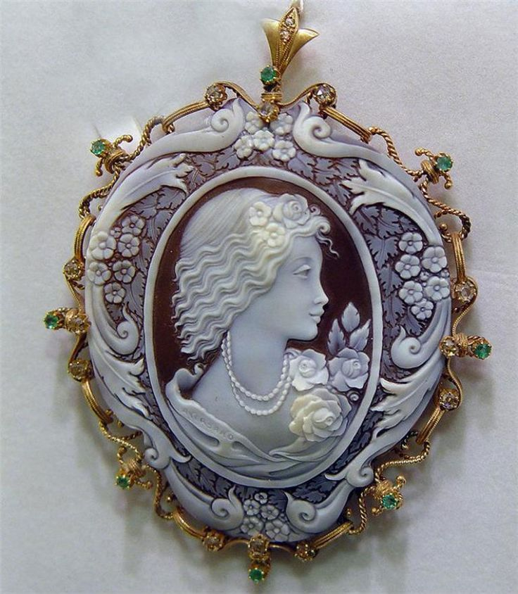 Hand-carved cameo set in 14k yellow gold surrounded by diamonds and emeralds.