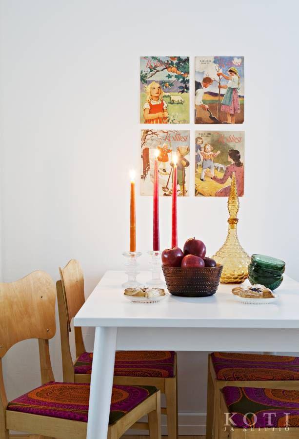 Vanhat aikakauslehden kannet ovat oiva pari 1950-lukua henkivälle Askon Pinna-ruokapöydälle. Tuolit on ostettu Kierrätyskeskuksesta ja päällystetty Marimekon Noitarumpu-kankaalla. Iittalan Festivo-kynttilänjalat ja Kastehelmi-astiat kruunaavat tyylin. Koti ja keittiö, kuva Kirsi-Marja Savola