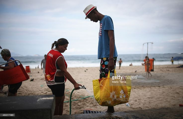 A man has his feet washed on Copacabana beach on July 28, 2015 in Rio de Janeiro, Brazil. The famed beach will host various Olympic events including beach volleyball, cycling, open water marathon and triathlon. August 5 marks the one-year mark to the start of the Rio 2016 Olympic Games.