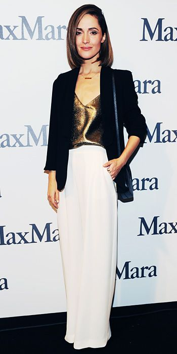 Rose Byrne wearing a black silk tuxedo jacket over a gold lame tank and cream silk trousers, all by Max Mara, accessorized with a delicate gold bar necklace.