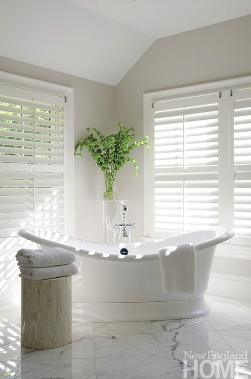 An Organized Nest - Spa like bathroom with greige walls and white plantation shutters. Spa-like tub sits at corner of bathroom in front of lucite plant stands as well as capiz stool over marble tiled floor.