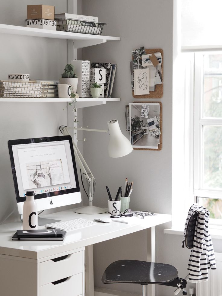 A lovely light home office with light grey walls and simple white shelving. The IKEA desk has been styled with an Anglepoise task light and monochrome accessories by Design Letters. Cork placemats have been cleverly upcycled to display inspiration