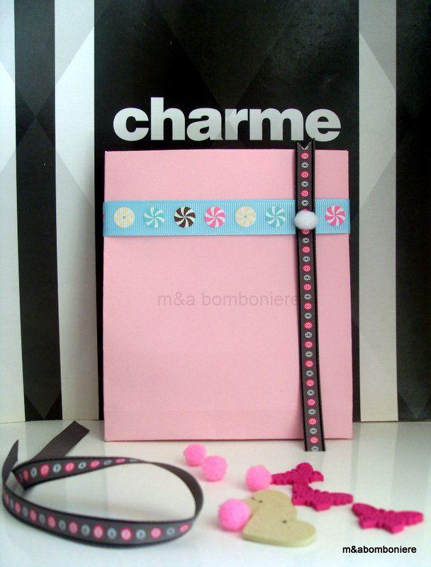 Ροζ σακουλάκι με πολύχρωμες κορδέλες και ένα γλυκό λευκό πομ πομ. Τιμή: 2,00 ευρώ.