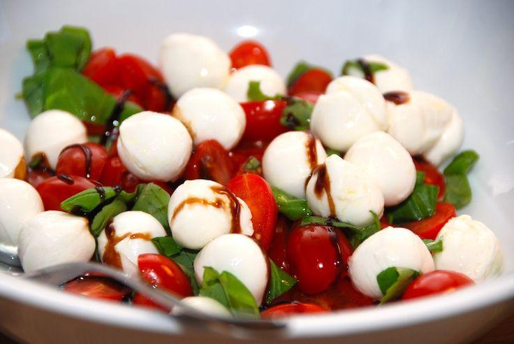 En god og hjemmelavet salat med mozzarella og tomater, der også vendes med lidt rødløg og basilikum. En god italiensk salat, der egner sig både som forret og tilbehør. Foto: Guffeliguf.dk.