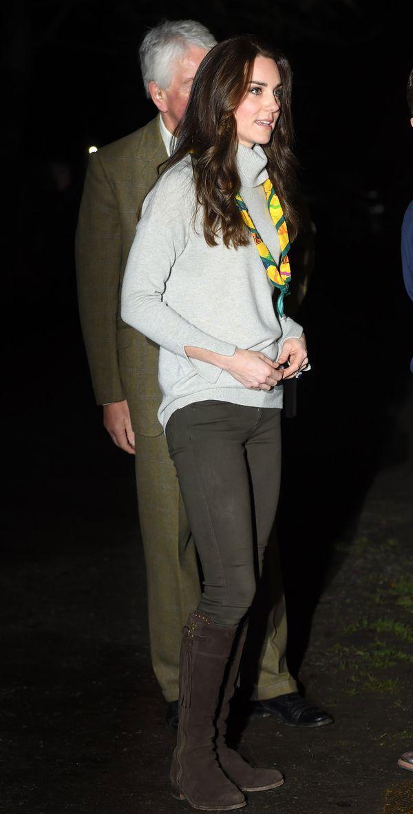 Kate Middleton usa calça skinny verde militar, tutrleneck cinza, lenço e bota marrom.