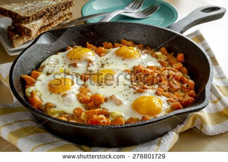 Fried eggs and sweet potato hash in cast iron skillet sitting on yellow striped kitchen towel with whole grain toast and stacked plates