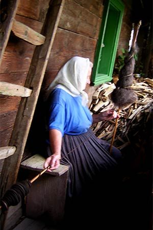 Budesti, Romania, old village woman hand spinning wool