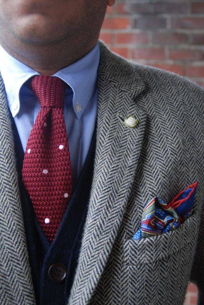 ヘリンボーンツイードジャケットに赤いネクタイと紺のベストを合わせた着こなし