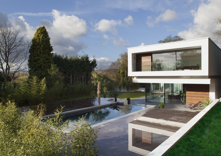 Award winning modern home in the Surrey countryside. the light filled open planned kitchen reflects in the external swimming pool while the bedrooms soar overhead.
