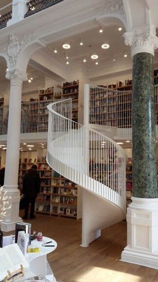 Gorgeous staircase flanked by two contrasting collumns. Beautiful bookstore architecture.