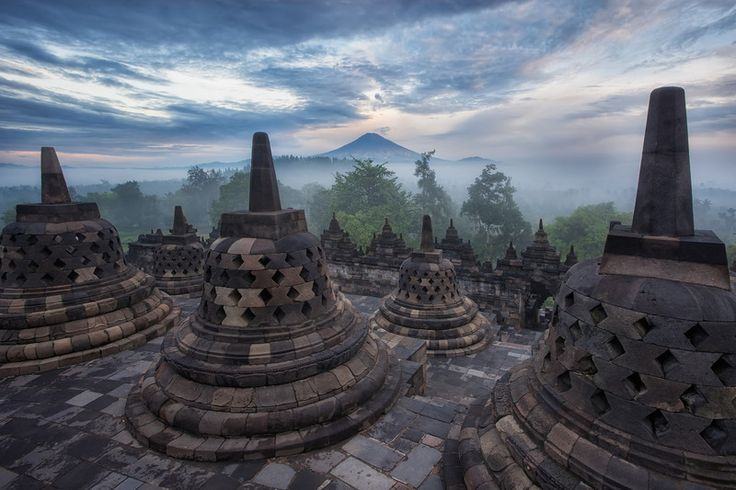 Photograph: Distant Volcano - Mount Merapi in the distance, seen through the stone stupas of Borobudur Temple in Indonesia