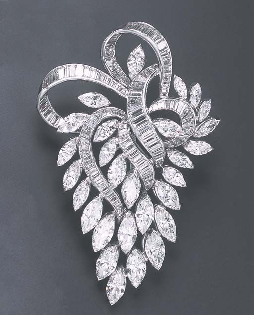 A DIAMOND BROOCH Designed as a baguette-cut diamond ribbon, extending a marquise-cut diamond openwork cascade, mounted in platinum