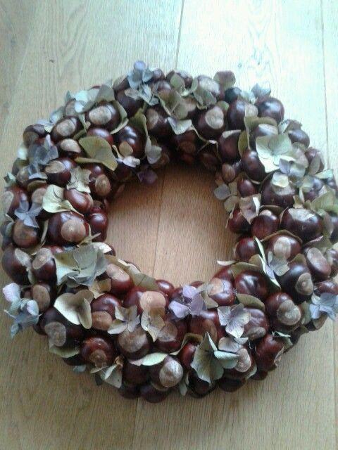 DIY Herfstkrans - lijm met een lijmpistool kastanjes en gedroogde hortensia blaadjes op een strokrans.