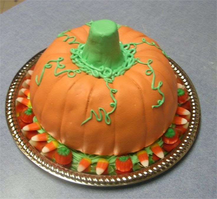 Pumpkin Cake - This is my 2nd cake I've made. it is for a cake walk at our Fall Festival at my church .. Spice cake made in a bundt pan turned upside down to make a pumpkin shape ( I don't have the pumpkin cake pan) Covered it with homemade marshmallow fondant and green bc. Stem is made with an ice cream cone covered in green mmf.. Placed candy around the bottom of the cake.