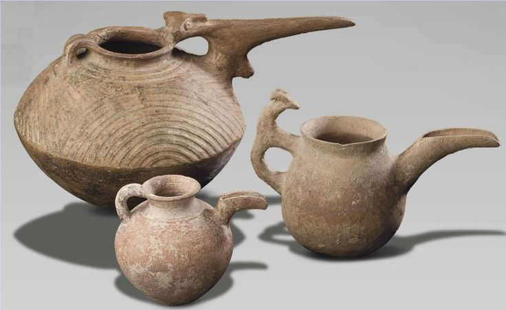 Iranian pottery spouted vessels, early to mid 1st millenium B.C.   Including a small globular jug, one with a goat form handle and one carinated, with a concentric semicircles incised on the top section, 41 cm long maximum. Private collection