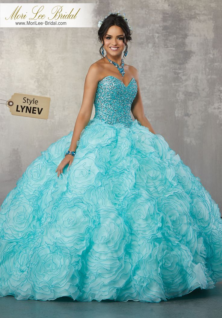 Style LYNEV Two-Tone, Allover Beaded Bodice on a Ruffled Organza Skirt Princess Perfect, This Quinceañera Ballgown Features a Fully Beaded Sweetheart Bodice and Floral Pattern Ruffled Skirt. Matching Bolero Jacket Included. Colors Available: Blush/Champagne, Deep Aqua/Light Aqua