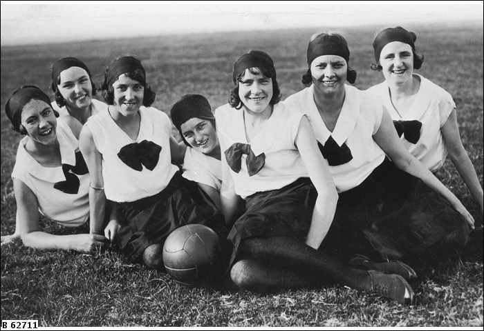 Womens' netball team 1925 Close view of members of the South Australian Farmers' Union netball team sitting together on a grass pitch; Florence May Killmier sits second from the right, she also had a distinguished career in rowing and was later President of the S.A. Womens' Rowing Association, other names not known - State Library of South Australia