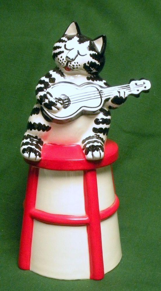 """MARKED ON BOTTOM """"B. KLIBAN TASTESETTER SIGMA"""". RARE KLIBAN CAT COOKIE JAR. Here is something for the discriminating Kliban Cat lover out there!KLIBAN CAT PLAYING GUITAR COOKIE JAR. This cookie jar is in excellent condition, with only 2 VERY minor chips in area that do not show. 