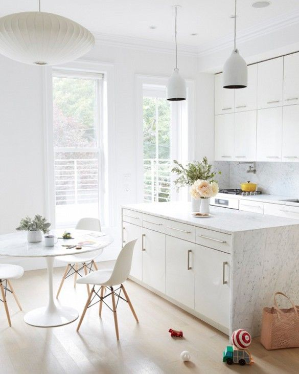 White marble kitchen with island, modern pendant lighting, a round table, a modern white and metal chairs.