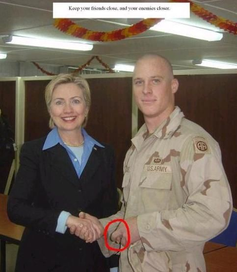"""This soldier has been thru Survival School & learned his lessons well. He's giving the sign of """"coercion"""" with his left hand. These hand signs are taught in survival school to be used by POW's as a method of posing messages back to our intelligence services who may view the photo or video. He was obviously being coerced into shaking hands with her. It's ironic how little she knew that he would so inform us about the photo-perhaps because she's never understood our military to begin with."""