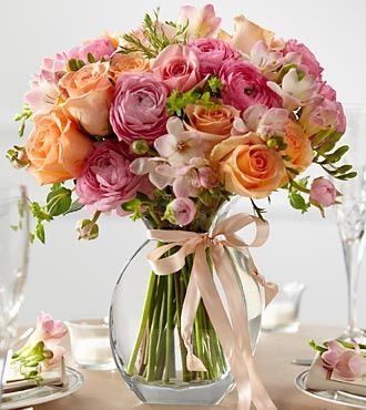 The FTD® Peach Silk™ Arrangement creates a sweet centerpiece to accent your tables for your formal occasion. Fresh peach roses, pink freesia, pink ranunculus, pink roses and lush greens are brought to