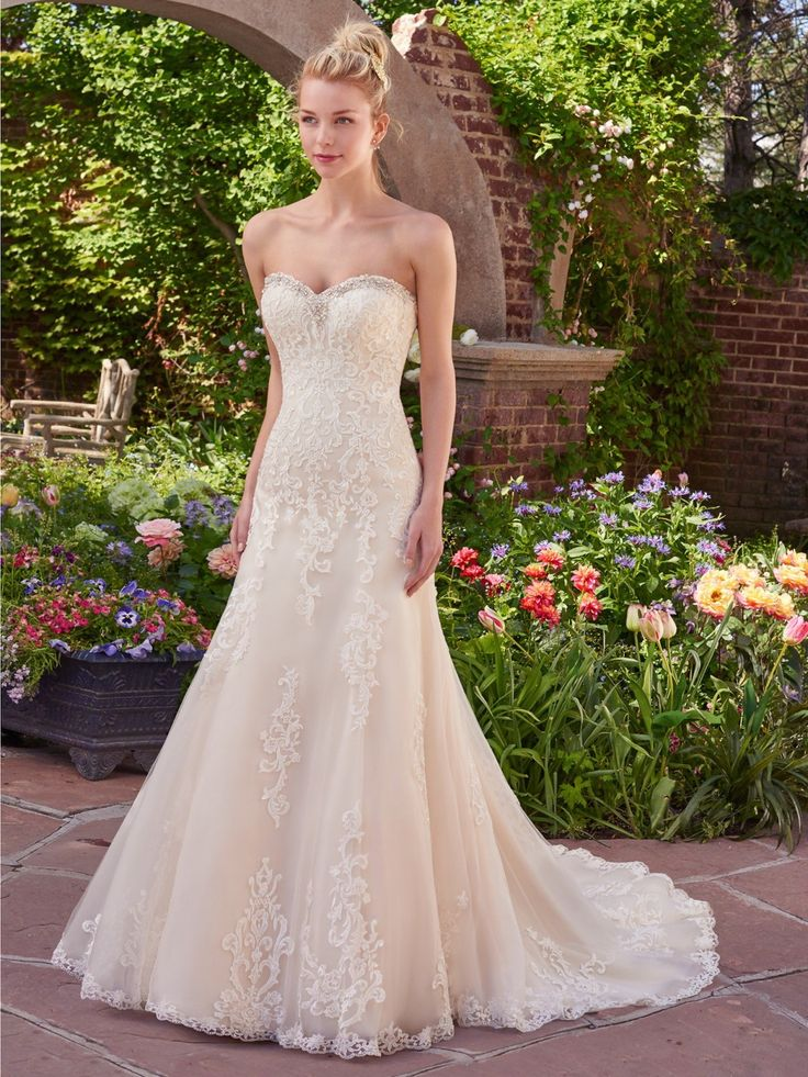 Layers of tulle and floral lace appliqués evoke antique romance in this fit-and-flare gown, featuring a sweetheart neckline and scalloped hem. Finished with corset closure. Detachable lace cap-sleeves sold separately.