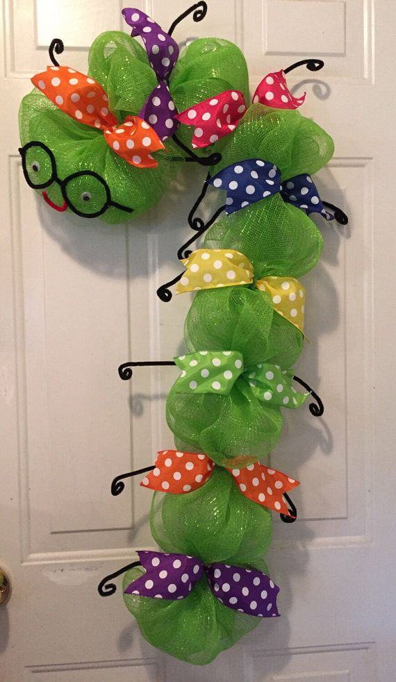 Back to school time is right around the corner and this bookworm wreath is the perfect back to school wreath, back to school decoration, gift for teacher, etc.... This cute bookworm measures 35 long X 18 wide. Made with lime green deco mesh. Decorated with multiple color polka dot wired ribbon, cute little black glasses and legs made out of black fuzzy sticks, and a red smile on its face. Available in most colors to match school colors. This adorable bookworm wreath is a great decoration to…