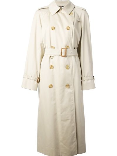 A classical garment. A must have. From A.N.G.E.L.O. VINTAGE PALACE Beige cotton 80s trench from Aquascutum featuring a classic collar, long sleeves with buckle strap cuffs, button shoulder tabs, a front double breasted button fastening, a waist belt, side pockets and a checked lining.