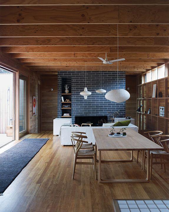 timber dark moody beams shelving clerestory windows pendant lighting fireplace mantle piece fire