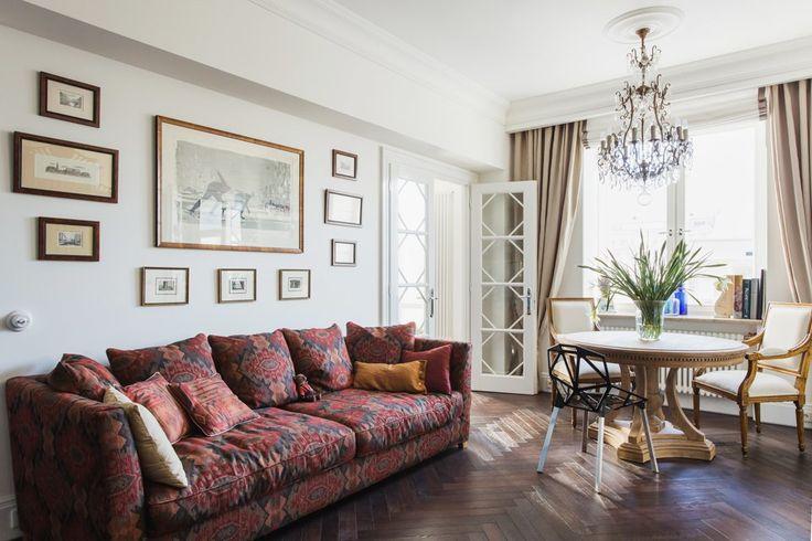 Светлая квартира архитектора всталинском доме. Гостиная стала главным помещением в квартире. Здесь разместили книжный стеллаж, старинный буфет для посуды в стиле ар-нуво, обеденный стол и диван. Из гостиной можно попасть во все помещения квартиры.