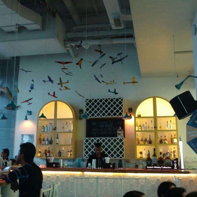 The colourful aeroplanes suspended from the tall ceiling is a fun decor in this happy place