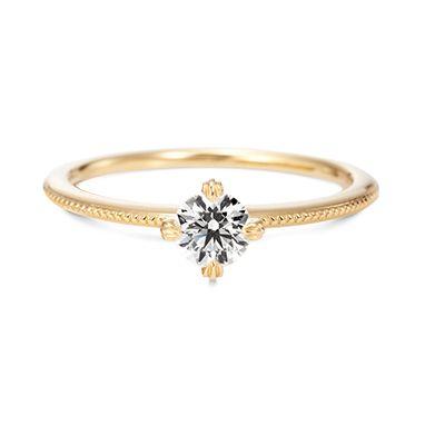 ブライトネス「クラシコ」(婚約指輪) ブライトネス「クラシコ」は、古典的なミル打ちをあしらったクラシカルなデザインの婚約指輪です。ずっと変わらない確かなもの(ふたりの愛)をコンセプトにした指輪です。 丁寧なミル打ちがリング一周に施されていて、ダイヤモンドに繊細な輝きを加えてくれるデザインです。 イエローゴールド以外にもプラチナなど好みの金属で作ることができます