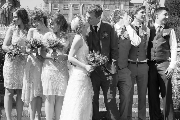 Black and white photo of bride and groom in the middle sharing  kiss whist the bridesmaids and ushers turn their heads to look away.