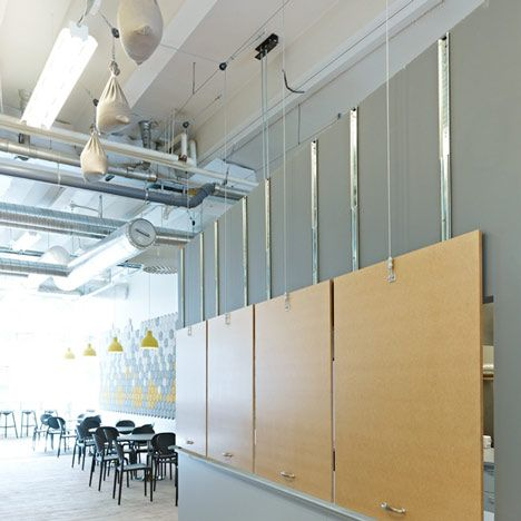 Re-configuring Space 2  Weighted hatches lift up to reveal a cafe counter at one end of the building, beside a line of black tables and yellow lampshades.