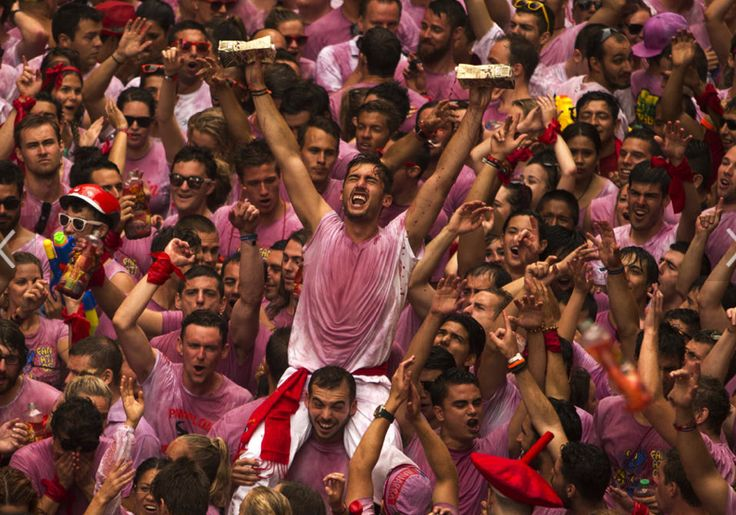 "Revelers from around the world turned out to kick off the festival with a messy party by throwing wine before the launch of the ""Chupinazo"" rocket, to celebrate the official opening of the 2014 San Fermin fiestas in Pamplona, Spain.  Pamplona town square, Sunday, July 6, 2014."