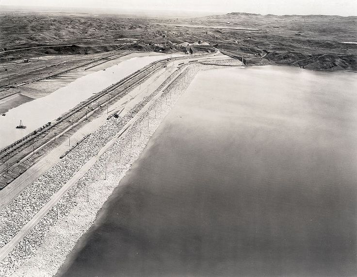 Aerial Fort Peck Dam before slide B - Fort Peck Dam - A view of the intact Fort Peck Dam during construction before the disastrous slide of September 22, 1938 which occurred at the far eastern end, located top center in this image. June 29, 1938. Courtesy, estate of Robert A. Midthun.