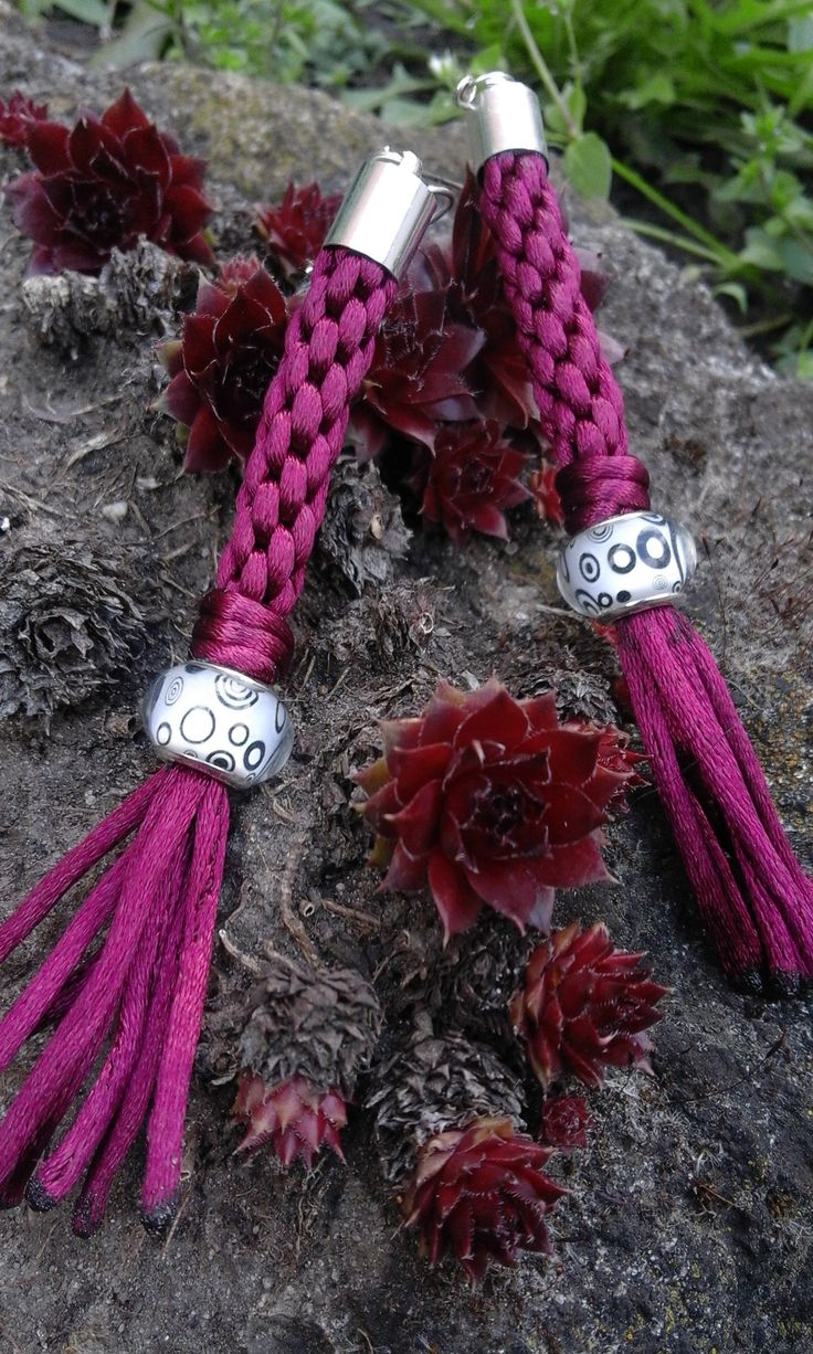 Claret earring pair of kumihimo thread and a white bead with black circles.