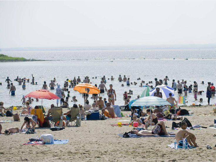People relax on the beach at Cap Saint Jacques nature park in Pierrefonds.