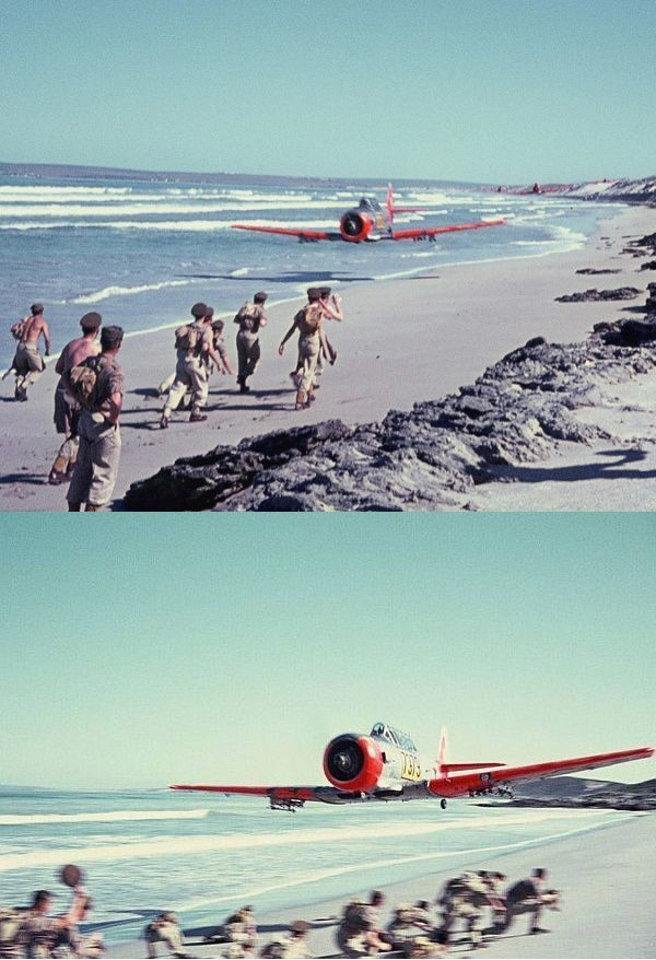MILITARY FIGHTER AIRCRAFT DOES LOW PASS ON THE BEACH AS TROOPS SCATTER AND DUCK!