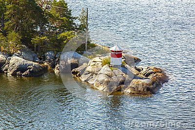White-red lighthouse on the edge of a rocky forest island on a sunny day, Scandinavia, Sweden, Stockholm